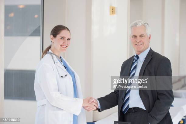Doctor and businessman shaking hands in hospital
