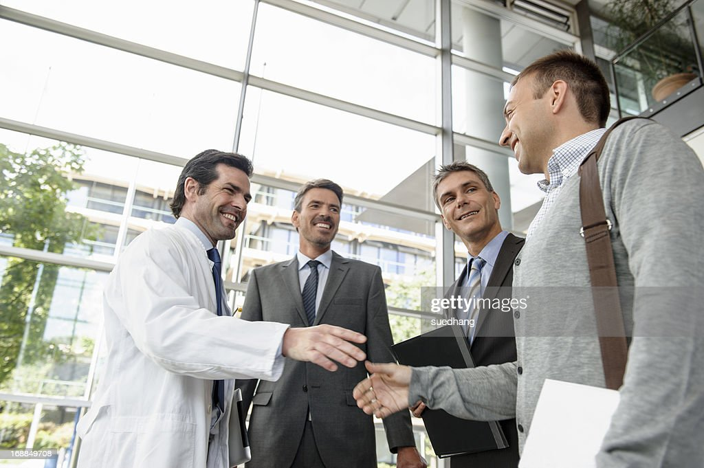 Doctor and businessman shaking hands : Stock Photo