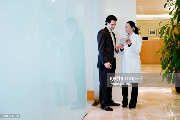 Doctor and businessman using digital tablet
