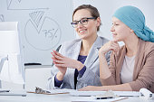 Young doctor talking with her cancer patient in an office