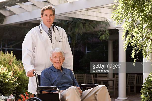 Doctor and elderly man in wheelchair outdoors