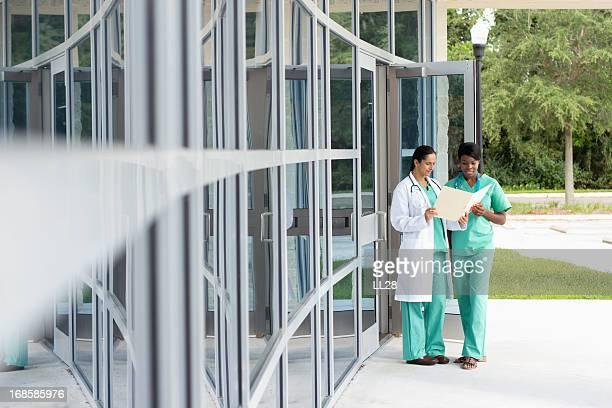 Doctor and her female nurse assistant outside a medical center