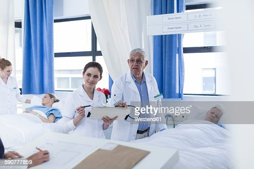 Sick Patient In Hospital Bed : Doctor and nurse at very sick patients bed in hospital