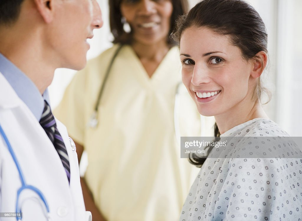 Doctor and nurse caring for female patient : Stock Photo