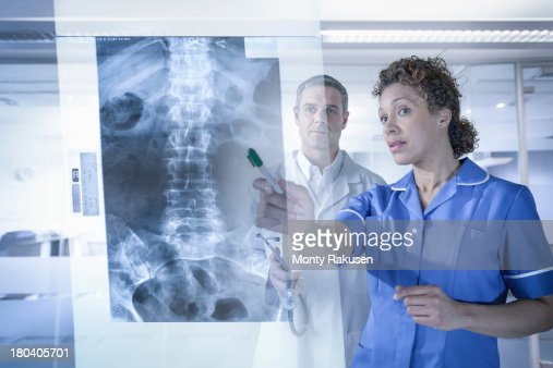 Doctor and nurse looking at xray results displayed on screen : Stock Photo