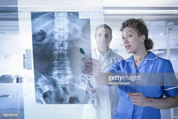 Doctor and nurse looking at xray results displayed on screen