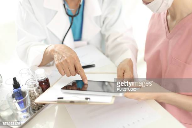 Doctor and nurse reading medical chart on digital tablet