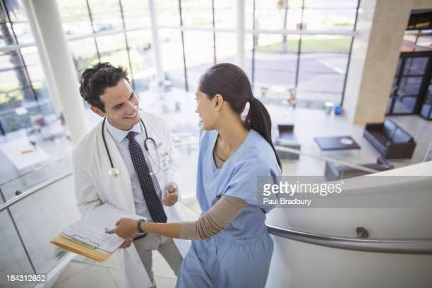 Arzt und Krankenschwester im Krankenhaus sprechen auf Treppe