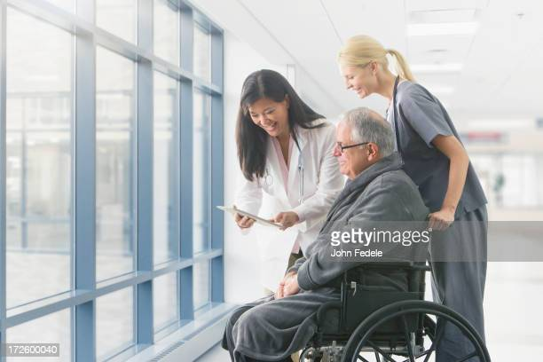Doctor and nurse talking to patient in hospital