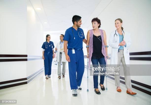 Doctor and nurse walking patient down hospital hallway