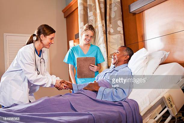 Doctor and nurse with patient in hospital bed