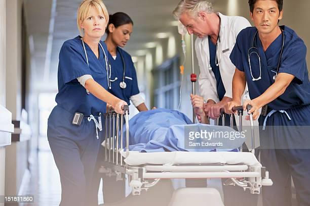 Arzt und Krankenschwestern wheeling Patienten im Krankenhaus-Rollbett down corri