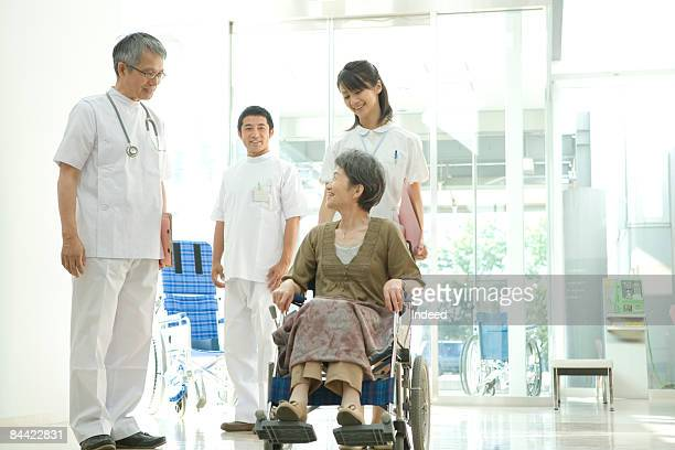 Doctor and patient in wheel chair talking