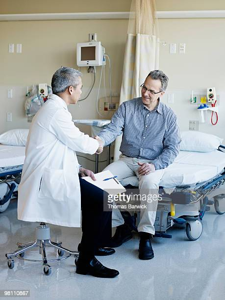 Doctor and patient shaking hands in hospital suite