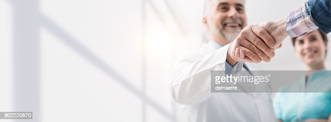 Doctor and patient shaking hands : Stock Photo