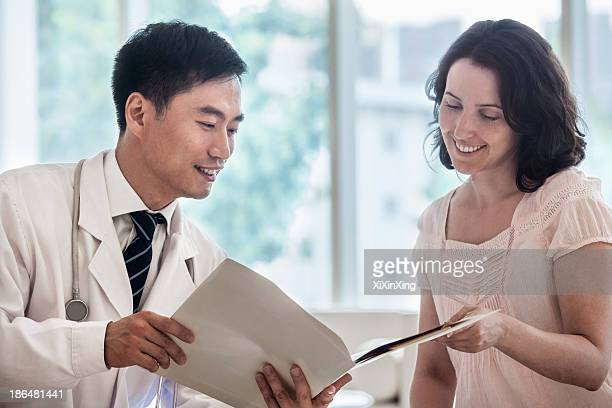 Doctor and patient sitting down and discussing medical record in the hospital