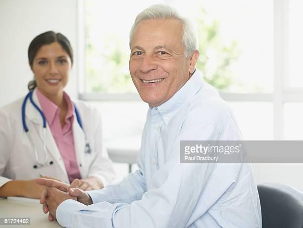Arzt und patient lächelnd sitzt im Büro