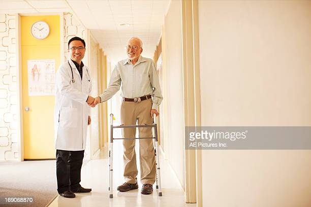 Doctor and patient smile shaking hands