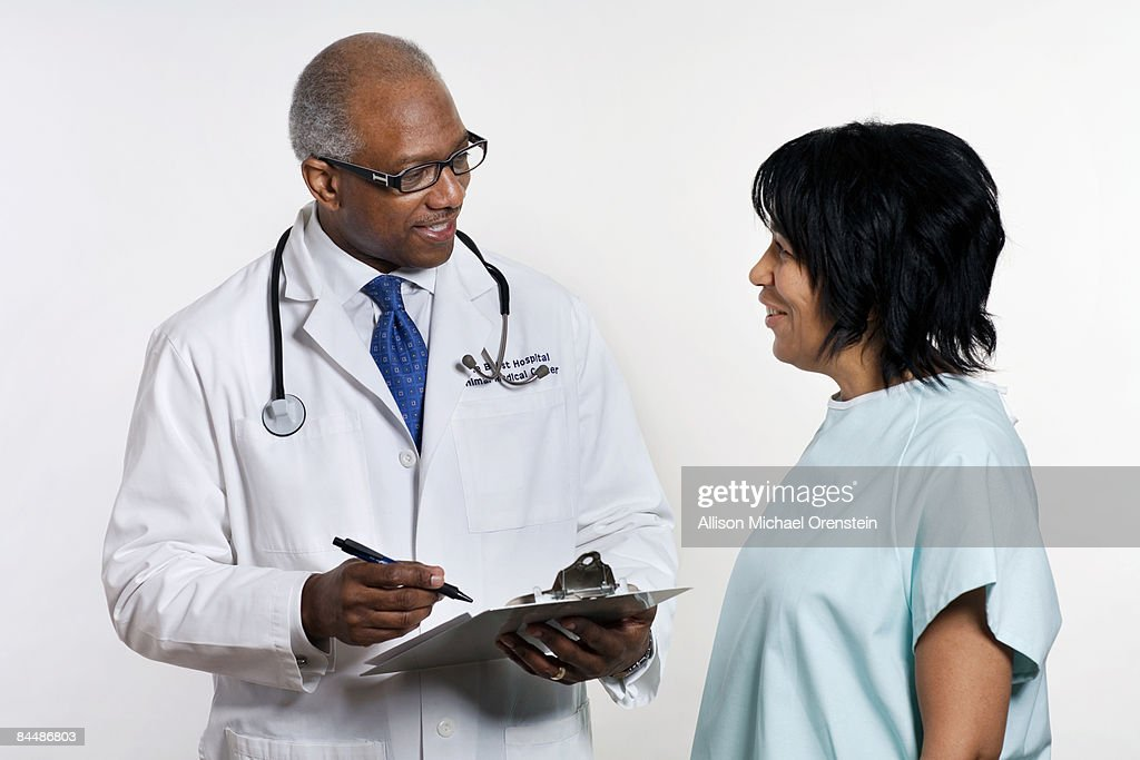 Doctor and patient talking to each other : Stock Photo