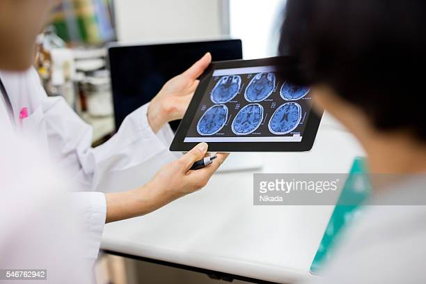 Doctor and patient using digital tablet in hospital