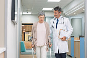 Mature doctor helping old female patient in crutches at the hospital. Physical therapist helping a woman on crutches in a medical clinic. Professional doctor and senior patient walking on hospital hal