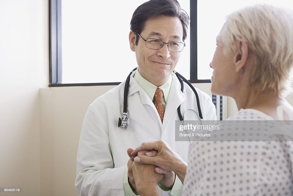 Doctor and patient with hands clasped
