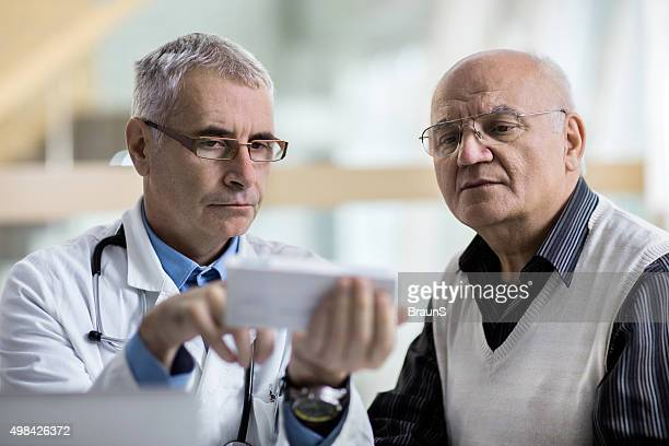 Doctor and senior man examining prescription medicine at doctor's office.