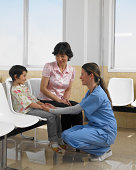 Doctor and woman talking to girl (5-7 years) in chair