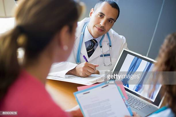 Doctor and Woman with X-ray on Laptop