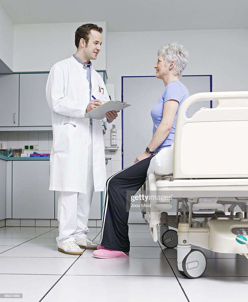 doctor asking female patient questions : Stock Photo