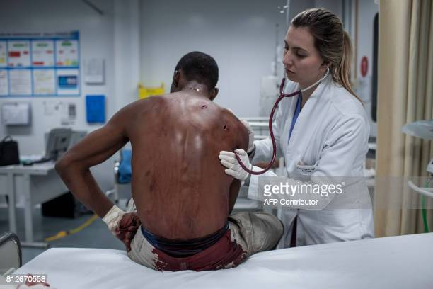 A doctor assists a patient who was stabbed twice in the back at the emergency room of the Cidade de Deus shantytown Emergency Care Facility in Rio de...