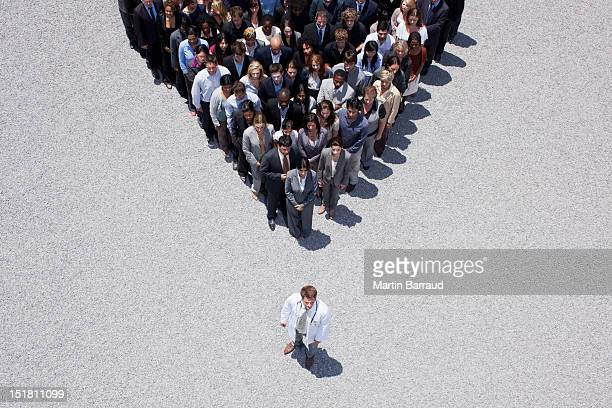Doctor at apex of pyramid formed by crowd