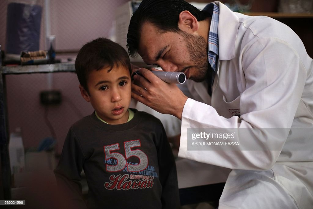 A doctor attends to a child at a clinic run by a local non-profit organisation called the Union of Free Syrian Doctors, in the rebel-controlled Syrian village of Utaya, in the eastern Ghouta region on the outskirts of the capital Damascus, on May 31, 2016. The non-government organisation offers medical services in the area in the absence of public services provided the state. / AFP / ABDULMONAM