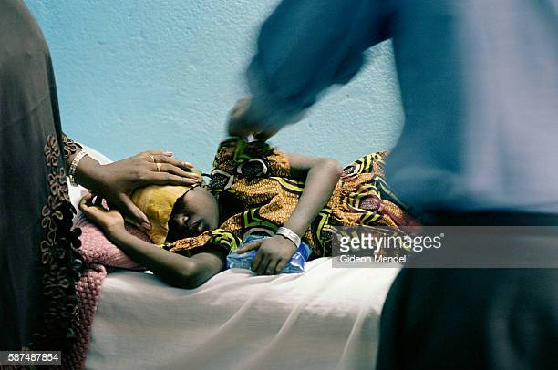 A doctor attends to a child with a high fever at the Oasis communitybased health centre Oasis which is a project of the nongovernmental organisation...