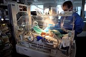 A doctor attends to a premature baby in an incubator at the neonatal ward of the Centre Hospitalier de Lens in Lens northern France on December 4...