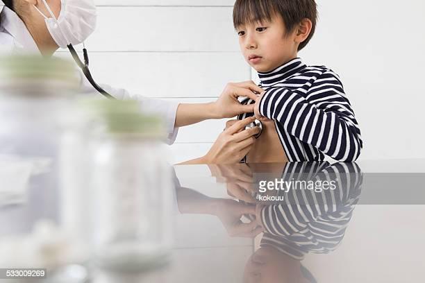 Doctor auscultating patient's heartbeat
