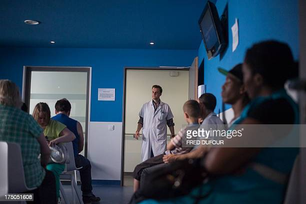 A doctor calls a patient in the waiting room at the surgery consultation on July 19 2013 at the Argenteuil hospital in a Paris suburb AFP PHOTO /...