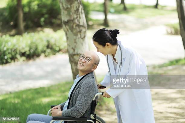 doctor caring for an elderly patient in a wheelchair