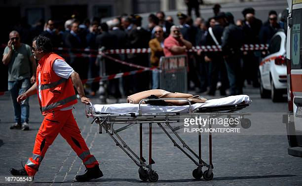 A doctor carriers a stretcher after a Carabiniere police officer was shot by a man in front of Chigi Palace in Rome on April 28 2013 Gunshots were...