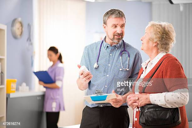 doctor chats to happy senior patient