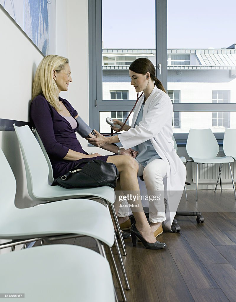 doctor checking blood pressure in waiting room : Stock Photo