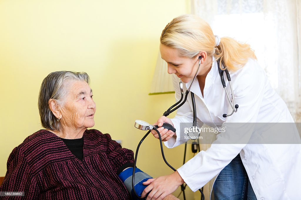 Doctor checking blood pressure on senior woman : Stock Photo