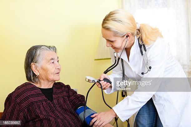 Médecin contrôle la pression artérielle de la femme âgée