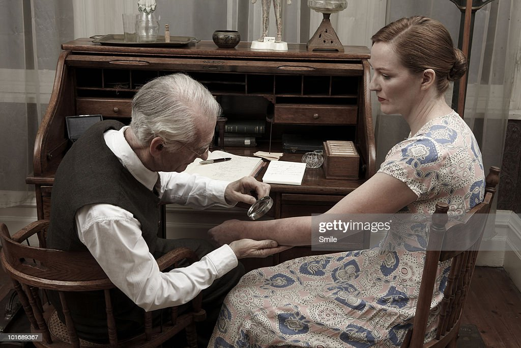 Doctor checking female patient's skin : Stock Photo