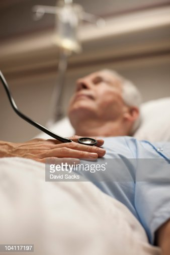 Doctor checking man's heartbeat with stethoscope : Stock Photo
