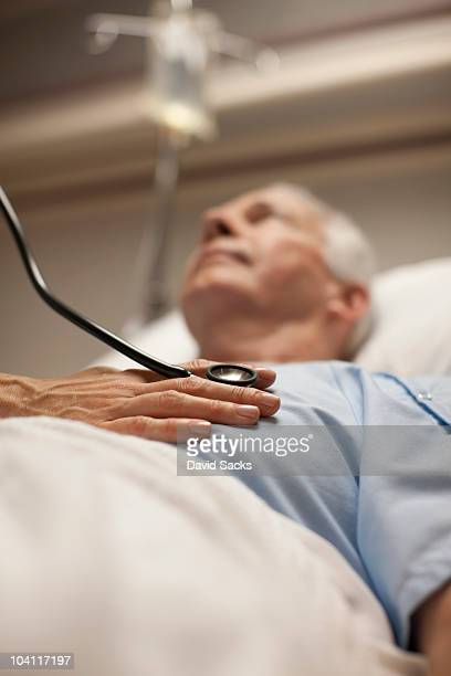 Doctor checking man's heartbeat with stethoscope
