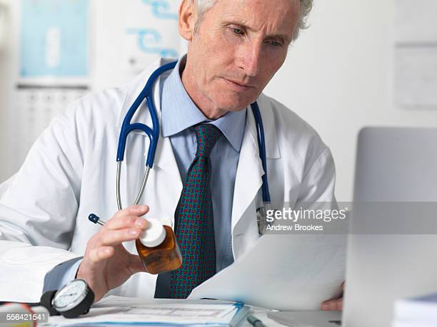 Doctor checking medical notes before prescribing drugs