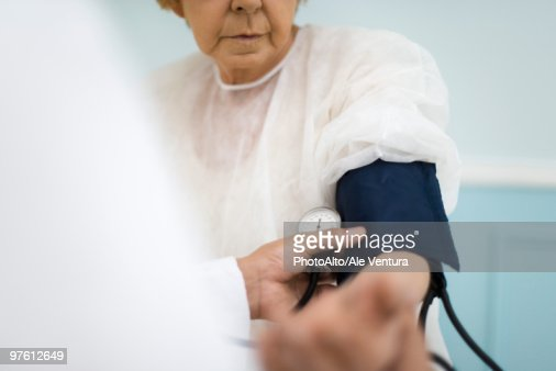 Doctor checking patient's blood pressure, cropped : Stock Photo