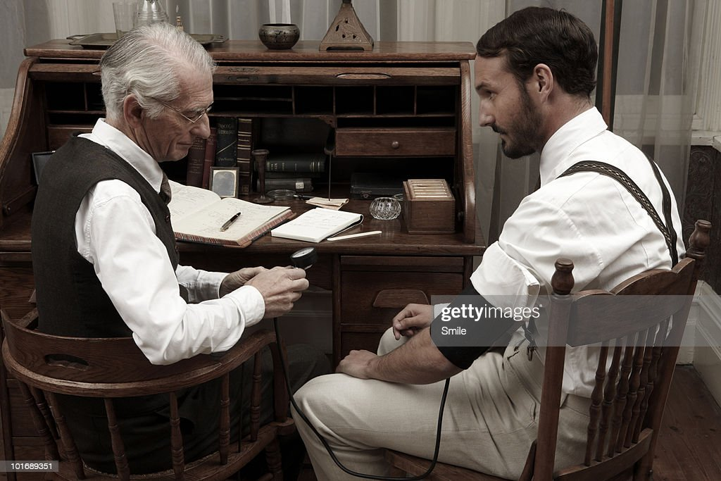 Doctor checking patient's blood pressure : Stock Photo