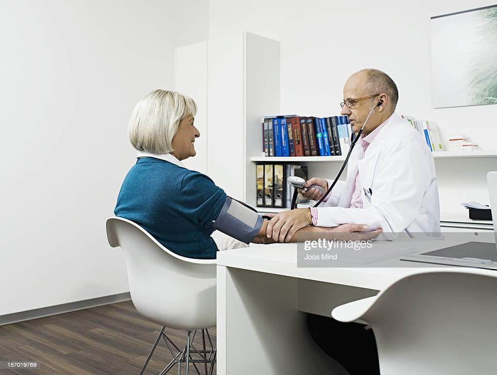 doctor checking patient`s blood pressure : Stock Photo
